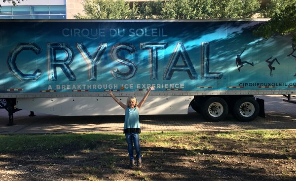 A photo of Krista in front of a Cirque du Soleil Crystal sign, one of our family experiences that helped me realize my favorite part of sharing custody